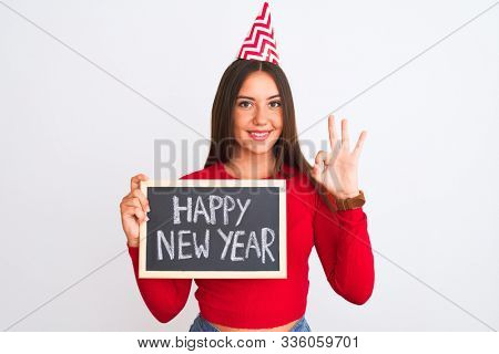 Beautiful girl wearing fanny party hat holding blackboard over isolated white background doing ok sign with fingers, excellent symbol