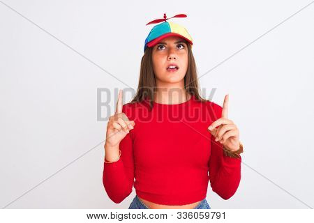 Young beautiful girl wearing fanny cap with propeller standing over isolated white background amazed and surprised looking up and pointing with fingers and raised arms.