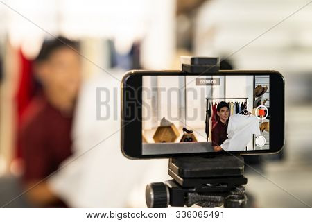 Young asian male online merchant fashion blogger using smart mobile phone to recording live vlog video for review casual wear clothes. Online influcencer on social media concept. Focus on mobile phone