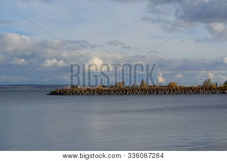 Breakwater From Beton Blocks On River Volga. Beautiful Landscape With Cloudy Sky.