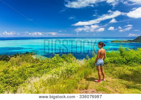 Bora Bora Tahiti cruise travel shore excursion tourist woman hiking on hike trail top view of lagoon and island, French Polynesia.