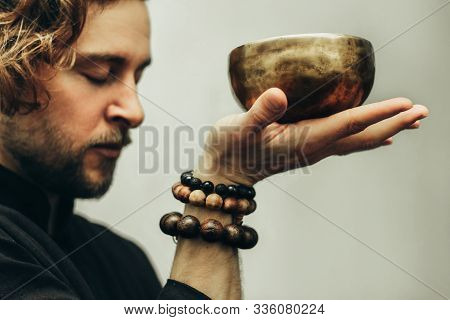 A Man With Closed Eyes Listens To The Singing Bowls. A Man Holds Singing Bowls In Front Of Him. The