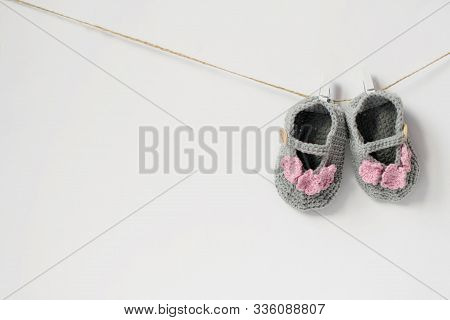 One Pair Of Booties For The Baby Hanging On A Rope. Baby Booties For A Little Girl Gray With Pink Fl