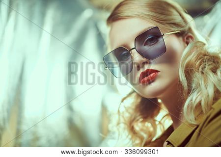 Fashion shot of a beautiful young woman in modern sunglasses. Optics and eyewear style.