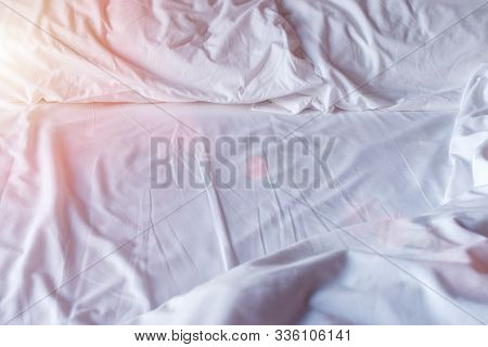 Crumpled White Bedclothes. Background With Sunny Light.