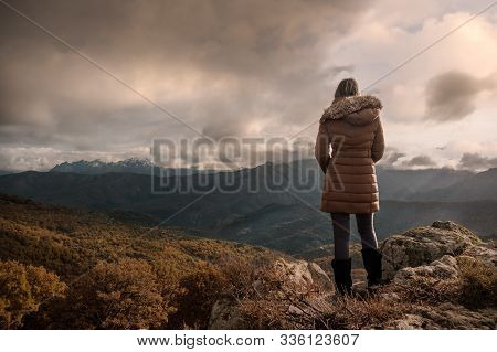 A Woman In A Brown Coat With Fur Collar Standing On A Hilltop In Corsica And Enjoying The View Of Th