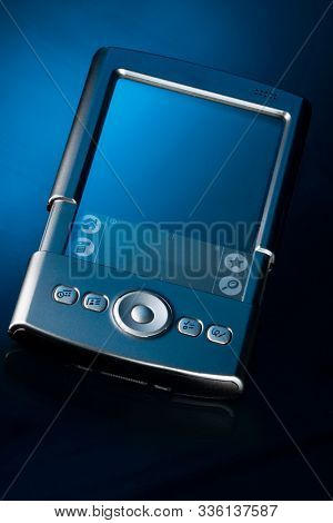 Old style PDA smartphone on isolated blue background.