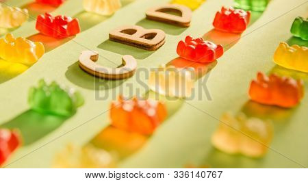Wooden Letters Cbd On A Green Background And Gelatin In The Form Of Bears. View From Above. The Shad