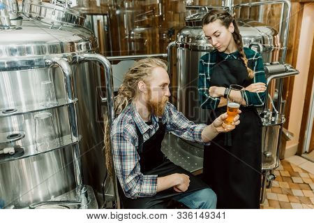 Brewery Workers Looking At Freshly Made Beer In Glass Tube And Discussing It. Male And Female Brewer