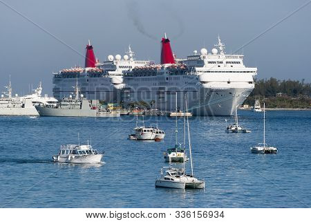 The View Of Yachts Drifting In Nassau Harbour With Moored Cruise Ships And Navy Ships In A Backgroun