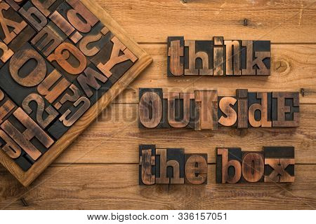 Think outside the box, phrase written with vintage letterpress printing blocks on rustic wood background.