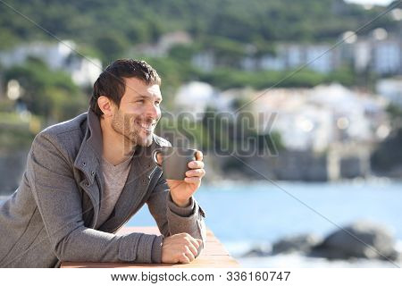 Happy Man Drinking Coffee Contemplating Views In Winter In A Balcony On The Beach