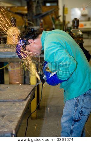 Metal Worker Using Grinder