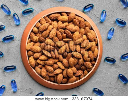Almonds As A Source Of Omega Fatty Acids In A Round Plate And Classic Blue Gelatin Capsules Scattere