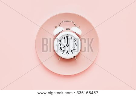 Intermittent Fasting Concept. White Alarm Clock On Empty Pink Plate. Top View, Copy Space.
