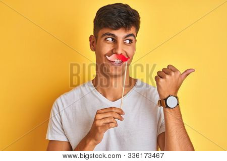 Young indian man holding fanny mustache standing over isolated yellow background pointing and showing with thumb up to the side with happy face smiling
