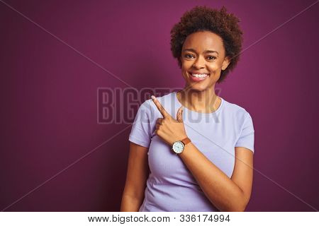 Young beautiful african american woman with afro hair over isolated purple background cheerful with a smile of face pointing with hand and finger up to the side with happy and natural expression
