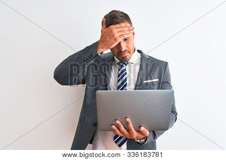 Young handsome business man working using computer laptop over isolated background stressed with hand on head, shocked with shame and surprise face, angry and frustrated. Fear and upset for mistake.