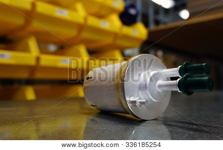 Concept New High Quality Original Spare Parts. New Original Fuel Filter On Blurry Background Of A St