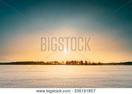 Sunset Sunrise Over Field Or Meadow. Sky Over Winter Snowy Ground. Landscape Under Scenic Sky At Sun