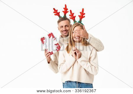 Image of man in Christmas reindeer antlers headbands giving New Year gift box to woman isolated over white background