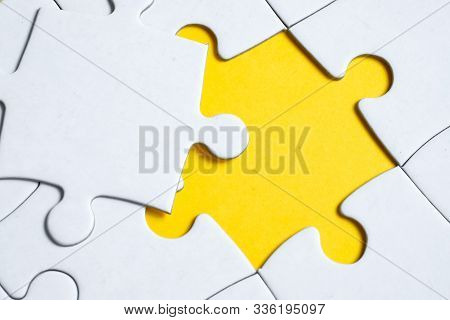Missing White Piece Lies On Jigsaw Puzzle On Yellow Background. Concept Of Completing The Final Puzz
