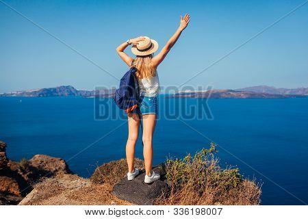Woman Traveler Raised Arms Feeling Happy Looking At Caldera From Akrotiri, Santorini Island, Greece.