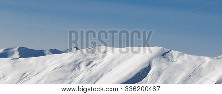 Panoramic View On Off-piste Snowy Sunlight Slope With Traces From Avalanches At Sun Evening. Caucasu