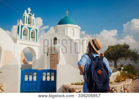Santorini Island Traveler Exploring Greek Church Architecture In Akrotiri. Woman Tourist Walking Dur