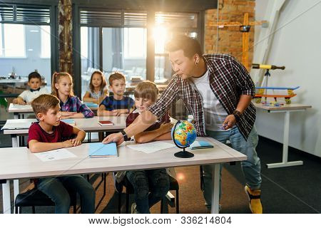 Teacher Of Elementary School Puts Notebooks On Desks Pupils For Learning. Group Of Schoolchildren Pr