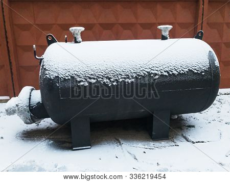 Black Industrial Capacitive Heater At Winter Under Snow Near Brown Concrete Fence. Heat Exchanger.