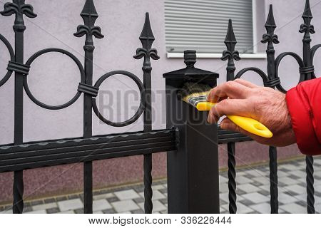Man Hand With Brush Painting Iron Fence
