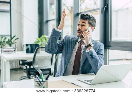 Discouraged Businessman Showing Indignation Gesture While Sitting At Workplace And Talking On Smartp