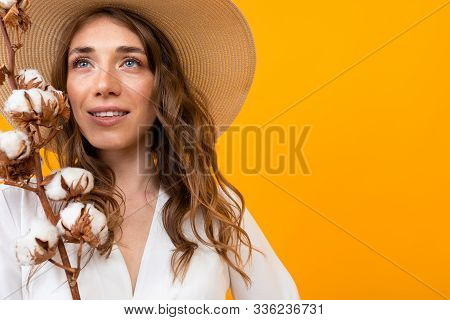 Portrait Of A Beautiful Girl With A Summer Hat With A Sprig Of Cotton On A Yellow Background.