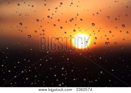 Water droplets on glass during a sunset poster