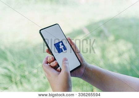 Chiang Mai, Thailand - Oct.18,2019: Woman Holding Xiaomi Mi Mix3 With Facebook App On The Screen. Fa
