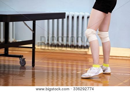 A Close-up Of A Young Girls Legs Is Tied With White Elastic Bandages At The Knees Next To A Tennis T