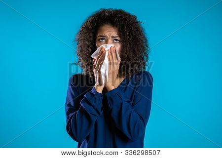 Young Girl With Afro Hair Sneezes Into Tissue. Isolated Woman Is Sick, Has A Cold Or Has Allergic Re