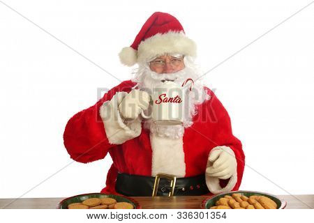 Santa Claus. Christmas Santa. Isolated on white. Room for text. Santa Claus holds a cup of Hot Coco with a Candy Cane and Whip Cream. Santa Loves Hot Coco and Cookies on Christmas.