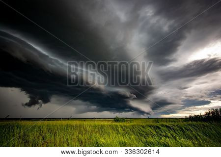 Dramatic Storm Clouds Over A Green Picturesque Field. Landscape The Gathering Storm.