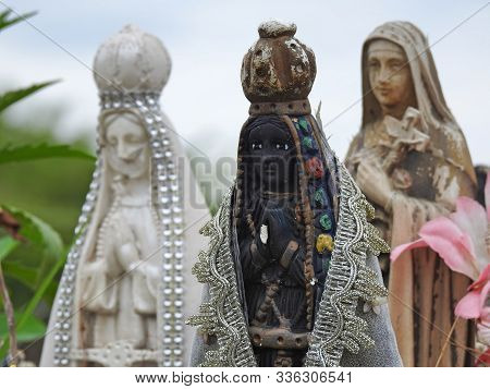 Scene In A Cemetery: Close-up Of A Statue Of Our Lady Of Aparecida, Patroness Of Brazil, With Claspe
