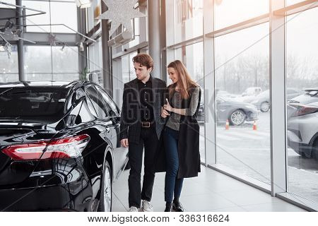 I Like This Car. Beautiful Young Couple Standing At The Dealership Choosing The Car To Buy.