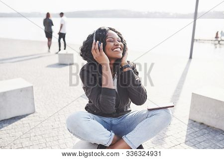Portrait Of A Beautiful Young Pretty African American Girl Sitting On The Beach Or Lake And Listenin