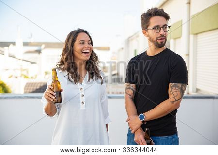 Happy Couple Talking, Laughing, Looking Away And Drinking Beer On Outdoor Terrace. Young Man And Wom