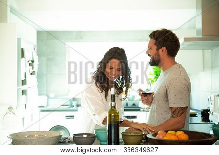 Cheerful Couple Drinking Wine, Laughing And Having Fun In Kitchen. Young Man And Woman In Casual Mee