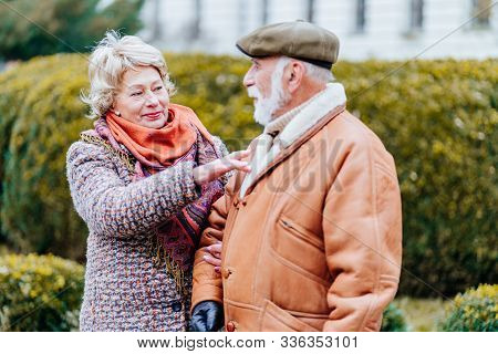 Old Couple Walking Outdoor. Eldrely Woman Care And Help Her Helpless Husband Protect Catch Cold , Co