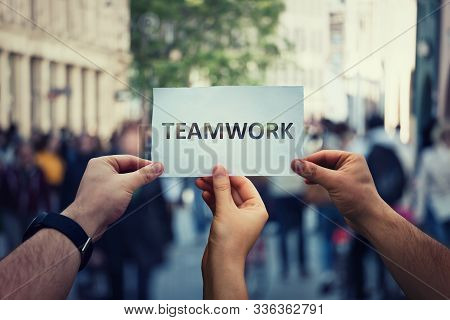 Diverse Hands Holding Together A Paper With Teamwork Text. Group Of Three People Unity And Team Conc