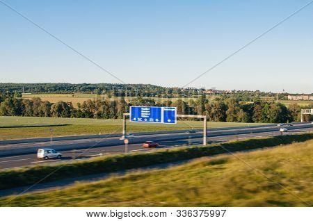Defocused View Of German Autobahn In Germany Near Frankfurt With Vivid Green Hills In Background