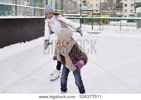 Smiling Young Mother And Her Cute Daughter Ice Skating Together. Family Skating And Training With Wh