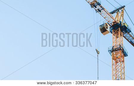 Close-up. Yellow Tower Cranes At Construction Site. Construction Site With Cranes Against Blue Sky.